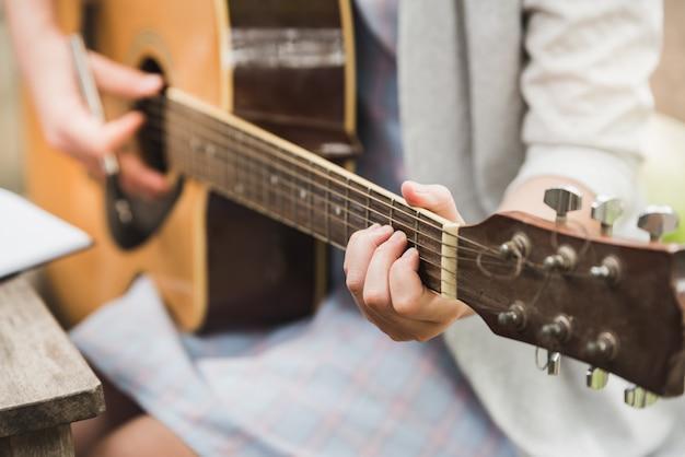 Girl playing acoustic guitar closeup