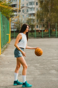 Girl playing basketball in urban environment
