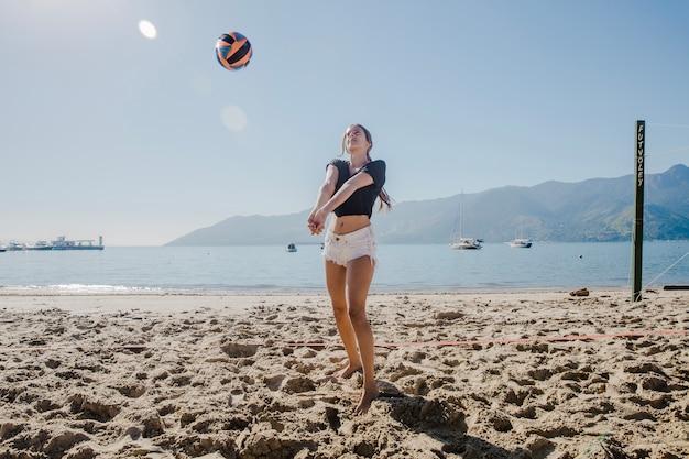 Девушка играет в пляжный волейбол