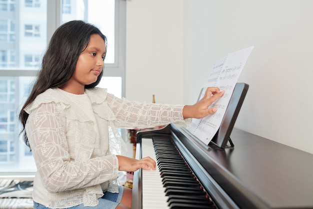 Girl playing the composition on piano