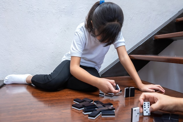 Girl playing domino inside the house