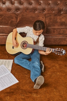 집에서 기타를 연주하는 소녀