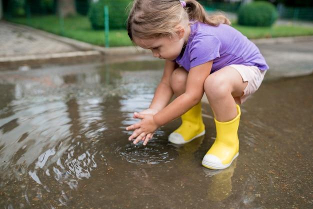 Девушка играет в луже после дождя