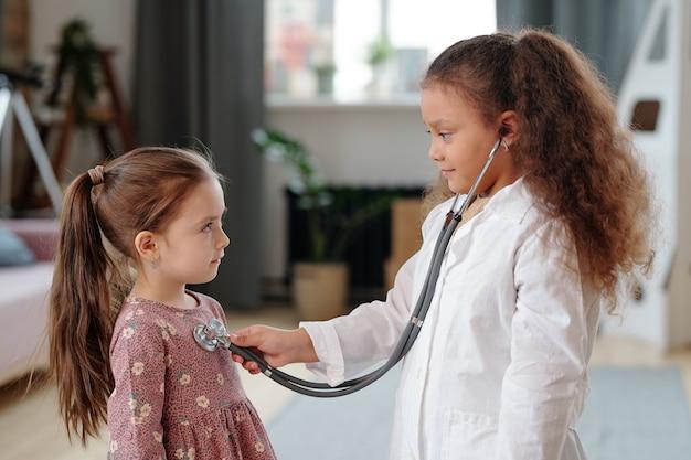 의사에서 놀고 집에서 노는 동안 어린 환자의 심장 박동을 듣는 소녀