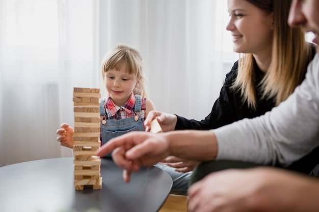 Girl playing jenga with crop parents