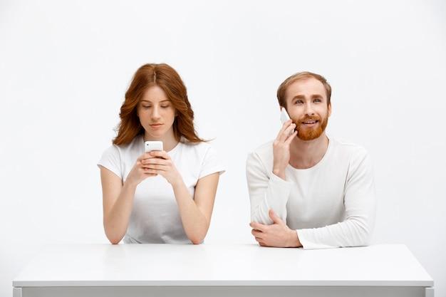 モバイルゲームをしている女の子、男は電話を話します