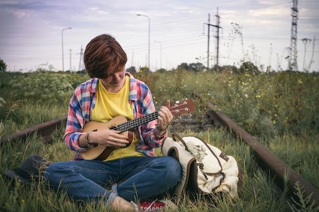 ウクレレで遊ぶ女の子。ギターのクローズアップを演奏する手