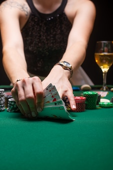 Девушка играет в покер и смотрит на карты