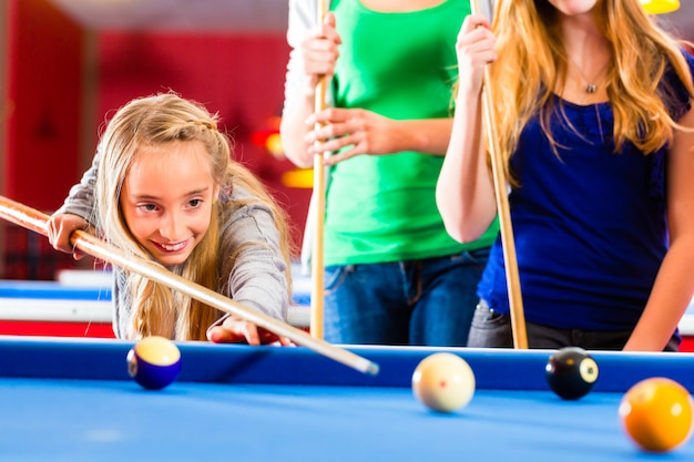 Girl playing pool billiard with family