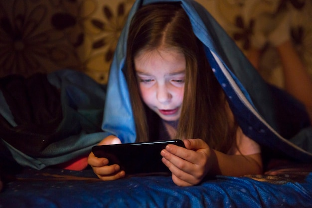 Girl playing smartphone game in dark room