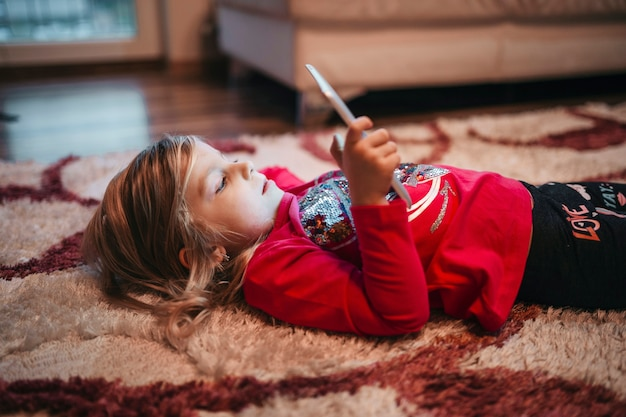 Girl playing tablet game on carpet