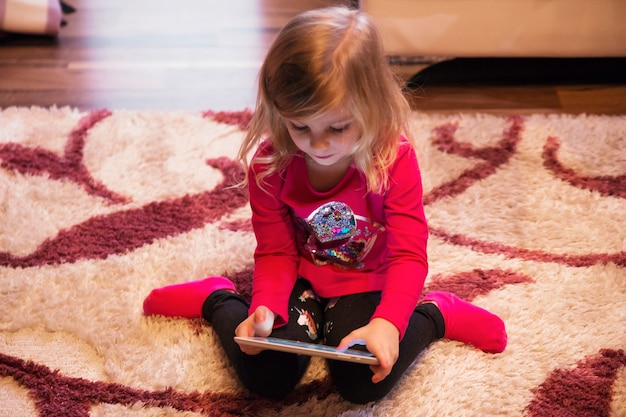 Girl playing tablet game on floor