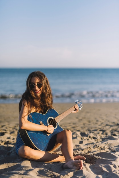 Girl playing the guitar sitting on the sand