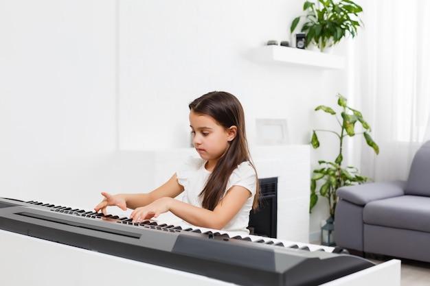 家でピアノを弾く女の子、オンラインで学ぶ