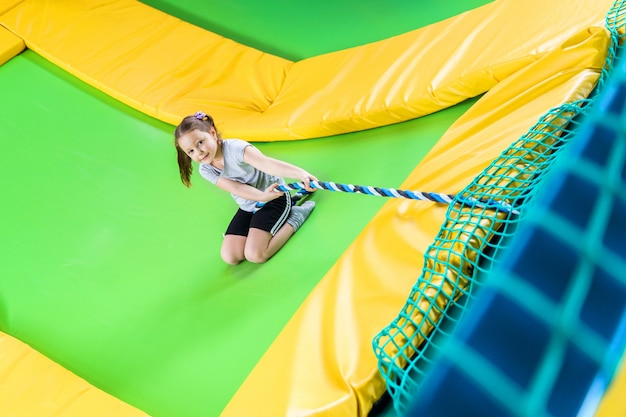 Girl playing in trampoline center jumping and climbing with rope