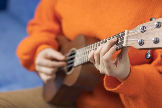 Girl playing the ukulele, close-up