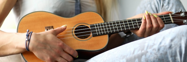 Girl playing on the ukulele at home