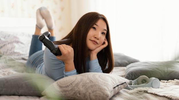 ベッドのフルショットでビデオゲームをしている女の子