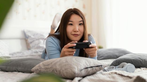 ベッドでビデオゲームをしている女の子