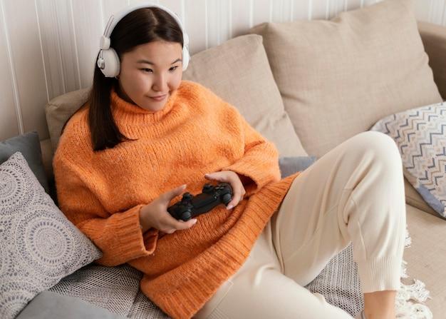ソファのミディアムショットでビデオゲームをしている女の子