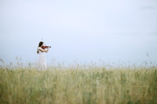 Girl playing the violin in the field