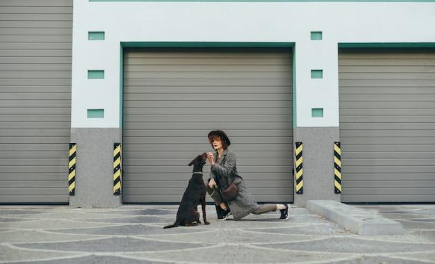 Девушка играет с собакой на прогулке