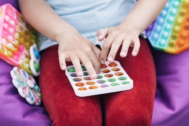 뽀삐 장난감을 가지고 노는 소녀 근접 촬영 어린이 손이 무지개를 가지고 노는 팝 it fidget toy