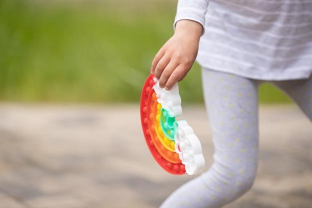 Девушка играет с радугой, хлопает игрушкой-непоседой