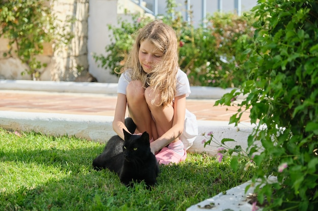 Girl playing with big black cat, outdoor, petting an animal. child and pet on green grass