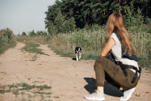 숲의 경로에 검은 색과 흰색 보더 콜리 강아지 강아지와 함께 연주 소녀