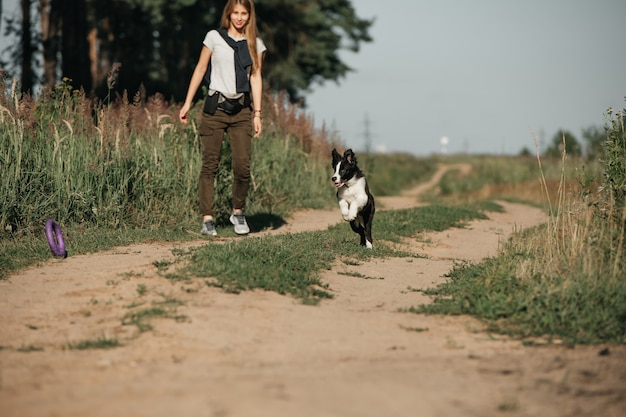 森の小道で黒と白のボーダーコリー犬の子犬と遊ぶ女の子