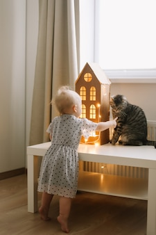 Girl playing with cat in cozy living room at home