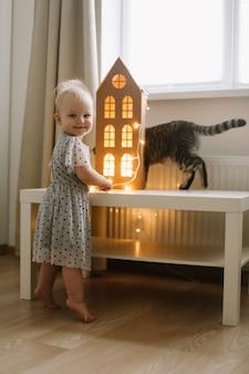 Девушка играет с кошкой в уютной гостиной дома