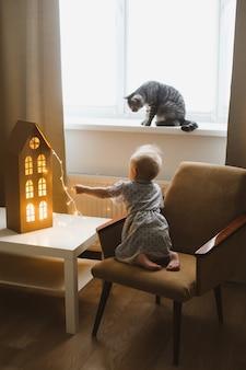 Девушка играет с кошкой в уютной гостиной дома Premium Фотографии