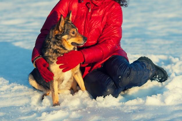 Девушка играет с собакой в заснеженном поле