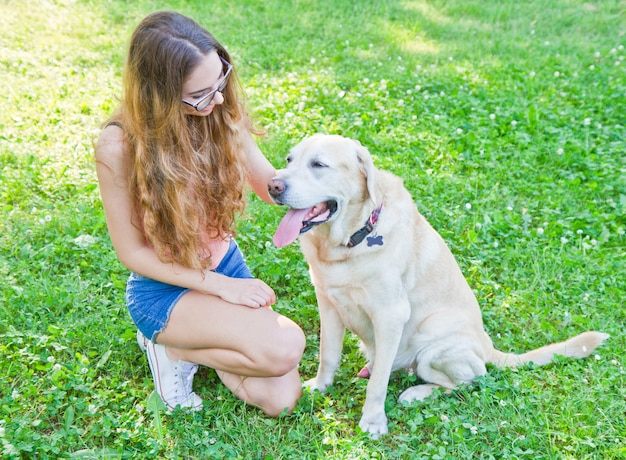 Girl playing with her labrador retriever dog in the park
