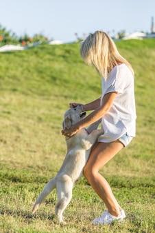 봄에 공원에서 그녀의 강아지와 함께 노는 소녀