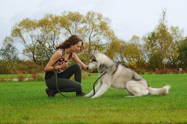 Girl playing with husky dog in city park. training the dog.