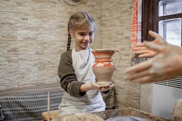 ワークショップ、クラフトアート、職人の趣味やレジャーでろくろでモデリング粘土で遊ぶ女の子