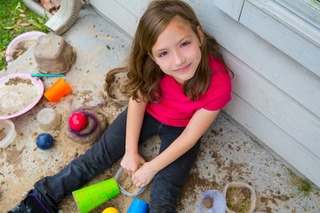 肖像画の笑みを浮かべて汚い土で泥で遊んでいるガールフレンド