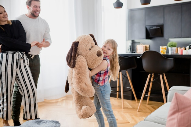 Girl playing with plush toy near parents