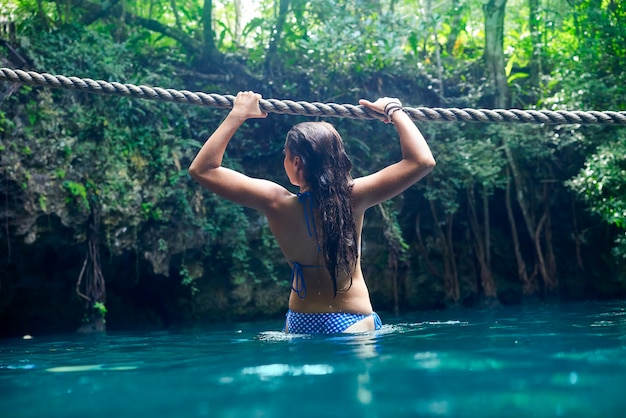 Girl playing with rope in cenote sinkhole