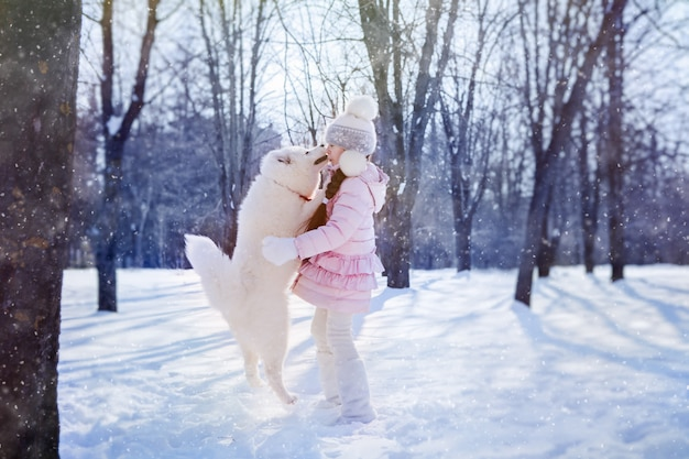 Girl playing with samoyed puppy in snow covered park on christmas morning