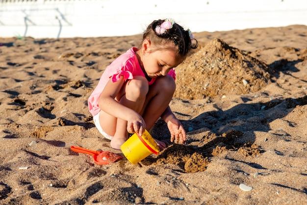 해변에서 모래를 가지고 노는 소녀 프리미엄 사진