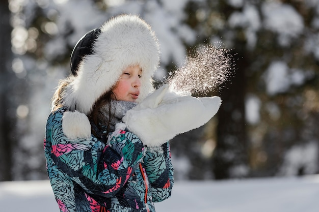 Girl playing with snow outdoors medium shot