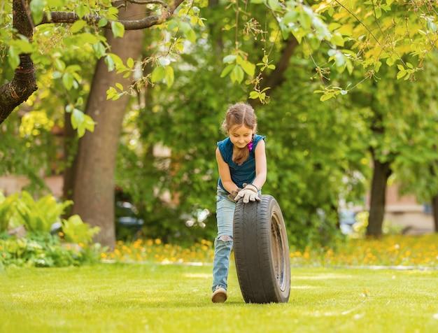 여름 공원에서 자동차의 바퀴를 가지고 노는 소녀