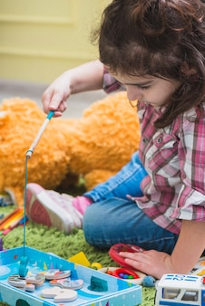 Girl playing with toy fishing rod