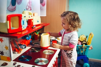 Girl playing with toy kitchen