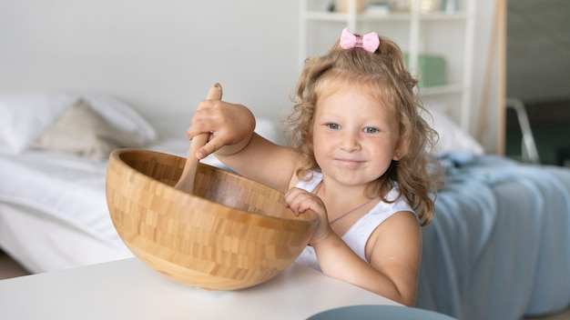 Girl playing with wooden bowl and spoon