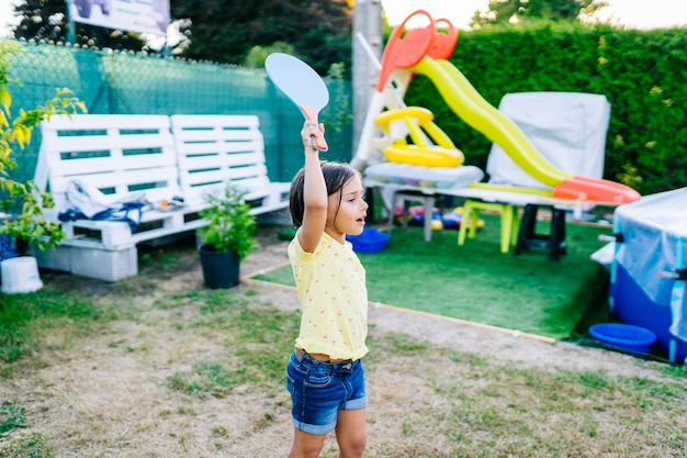 A girl plays beach tennis in a garden with a pool and toys on summer